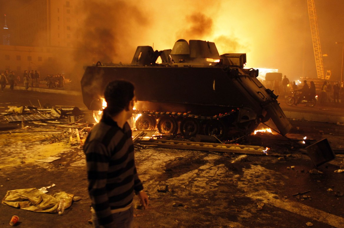 A protester looks at a burned Egyptian Army armoured vehicle in downtown Cairo on January 28.  [Goran Tomasevic/Reuters]