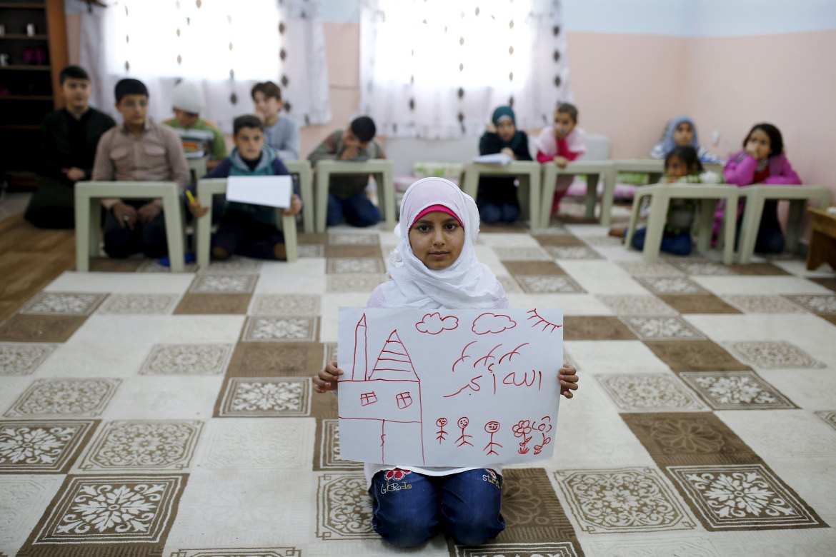 "Islem Halife, 11, shows a drawing of her home in Syria as she sits in a classroom where she learns the Koran at the Nizip refugee camp in Gaziantep province, Turkey. The writing in Arabic in the drawing reads, ""God is great."" [Umit Bektas/Reuters]"