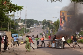 Anti-government protesters block a road and burn tyres during a protest last year against a law that could delay the elections due to be held at the end of 2016 [John Bompengo/AP]
