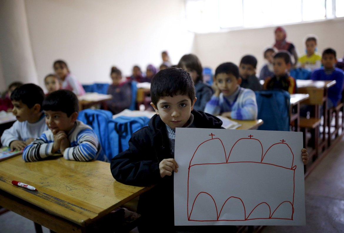 Ali Ristmo, 7, shows his drawing depicting a mosque during a lesson with his classmates at the Yayladagi refugee camp in Hatay province, Turkey. [Umit Bektas/Reuters]