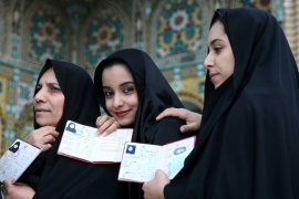 Iranian women queue in a polling station to vote for the parliamentary and Assembly of Experts elections in Qom [AP]