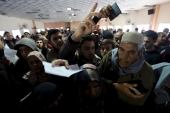 Palestinians present their documents as they wait for travel permits to cross into Egypt at the Rafah border crossing [REUTERS]