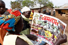 Refugees from South Sudan look at a photo montage depicting the conflict in their country on a calendar at the Kyangwali refugee settlement in Hoima district in Uganda [Thomas Mukoya/[Reuters]