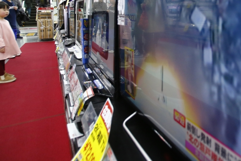 Children watch TV screens reporting North Korea's rocket launch at an electronics store in Tokyo, on February 7 [AP]
