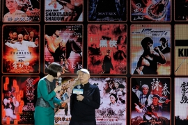 Director Yuen Wo-ping speaks on stage as a screen shows action movies directed by him, during a press conference for the movie Crouching Tiger, Hidden Dragon: Sword of Destiny [AP Photo/Andy Wong]