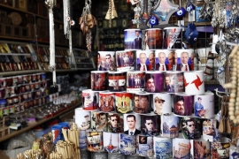 A shop sells mugs with photos of Bashar al-Assad, Vladimir Putin and Hezbollah leader Hassan Nasrallah in Damascus, Syria [EPA]