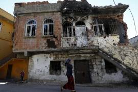 A woman walks past a building which was damaged during the security operations and clashes between Turkish security forces and Kurdish militants, in the town of Silvan in Diyarbakir. [Reuters]