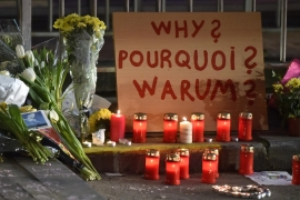 A sign in English, French and Flemish behind candles and flowers near the Maelbeek metro station, in Brussels [AP]