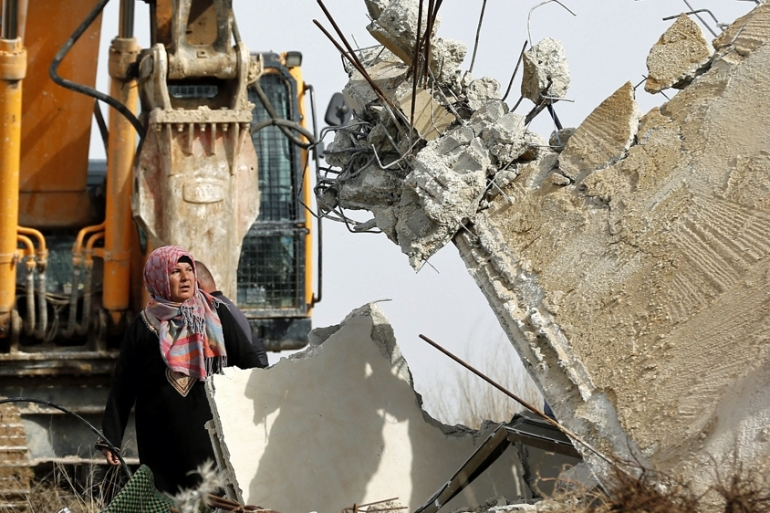 A Palestinian woman stands in front of Israeli bulldozers to stop them during the demolition of a house owned by Palestinians in the West Bank village of Biet Ula, January 2016. [EPA]