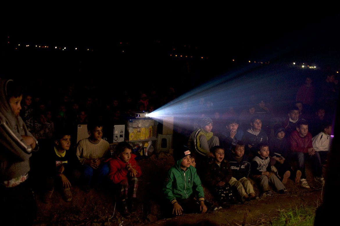 Volunteers in Idomeni set up an open-air cinema using a projector to cheer up the children staying at the camp. [Paulo Nunes dos Santos/Al Jazeera]