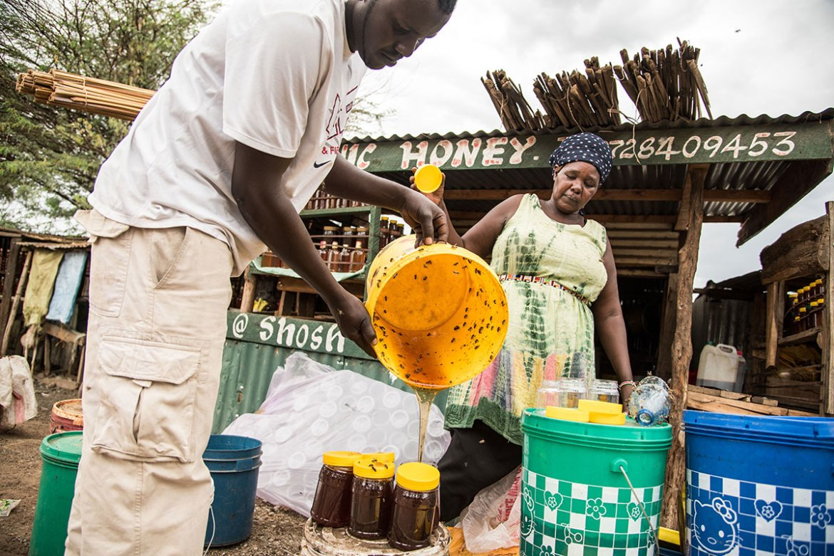 Agnes Cheptepkeny and her son process the honey. 'This is my bank,' says Cheptepkeny , pointing to honey buckets. When she needs cash, she buys honey, processes it and sells it on. [Berta Tilmantaite/Transterra Media/Al Jazeera]