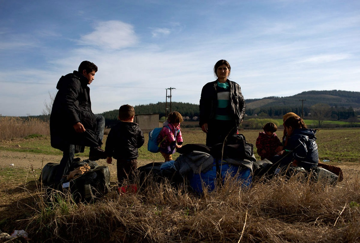 A group of Kurdish-Syrian refugees rest in a field during their journey towards the Greek-Macedonian border. [Paulo Nunes dos Santos/Al Jazeera]