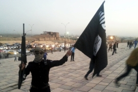 An ISIL fighter holds an ISIL flag and a weapon on a street in the city of Mosul, Iraq [Reuters]