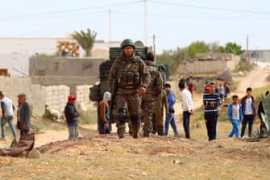 Tunisian soldiers patrol Ben Gardane a day after deadly clashes with fighters near the border with Libya [EPA]