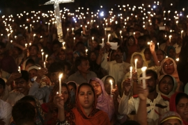 Pakistani Christians hold candles during a vigil for victims of a deadly suicide bombing in Lahore, Pakistan [AP]