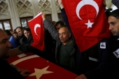 Men hold Turkish flags over the coffin of a car bombing victim during a commemoration ceremony in a mosque in Ankara, Turkey, March 14, 2016. [Reuters]