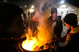 Stranded refugees warm up by a fire at Polikastro station, 20km from the Greek-Macedonian border [Nicola Zolin/Al Jazeera]