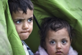 Children peer from a tent at a northern Greek border station [AP]