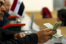 A customer checks his US dollar notes in a bank in Cairo, Egypt [REUTERS]