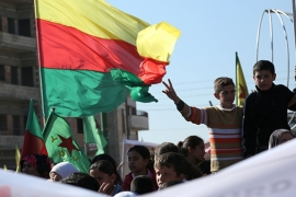 Kurdish children flash the sign for victory next to a flag of the PYD during a demonstration against the exclusion of Syrian-Kurds from the Geneva talks in the Syrian city of Qamishli  [Getty]
