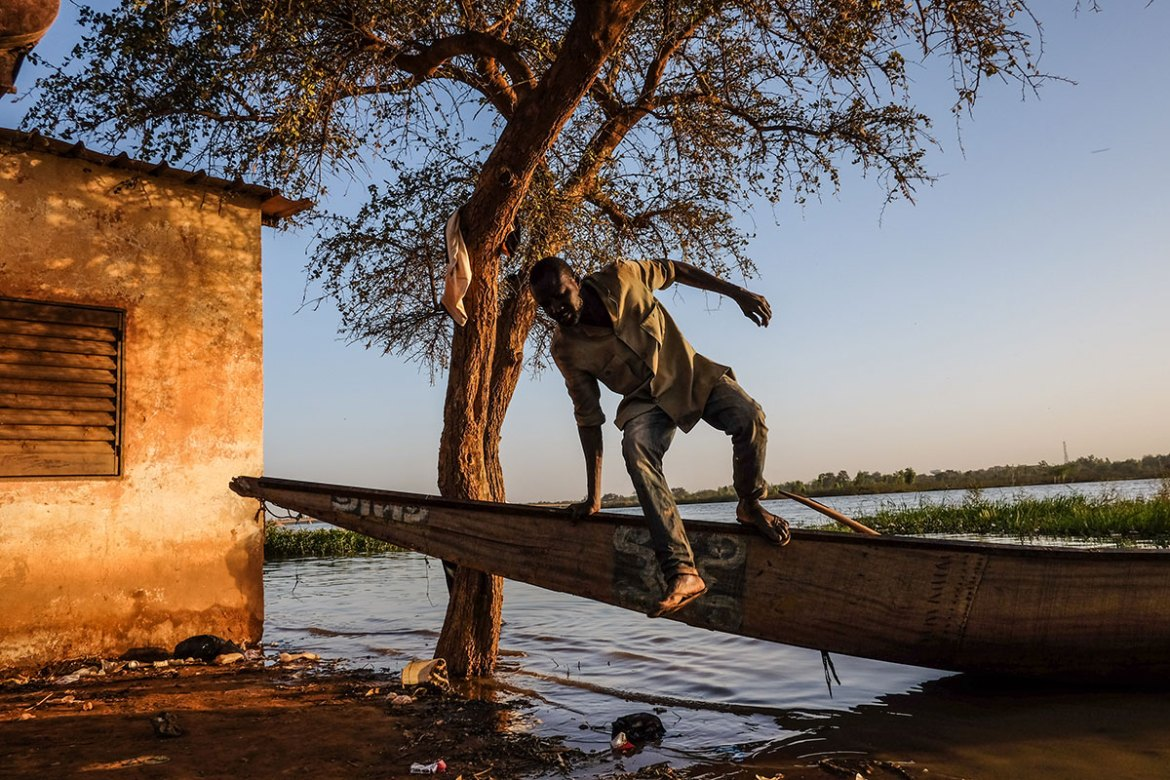 A man jumps out of a canoe in Niamey  by the Niger River. [Ricci Shryock/Al Jazeera]