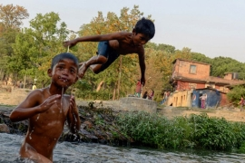 Nepalese boys swim in a river as they beat the summer heat in Kathmandu [Prakash Mathema/AFP]