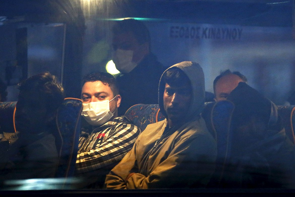 People are seen on a bus before boarding a Turkish-flagged passenger boat to be returned to Turkey. [Giorgos Moutafis/Reuters]