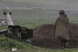 An Armenian soldier in Nagorno-Karabakh stands near an artillery unit in the town of Martakert. [Reuters]