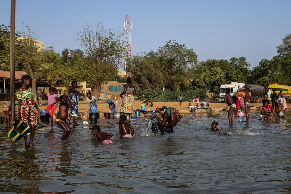 Women and young girls carry out their daily chores and use the river to cool off in Niamey. [Ricci Shryock/Al Jazeera]