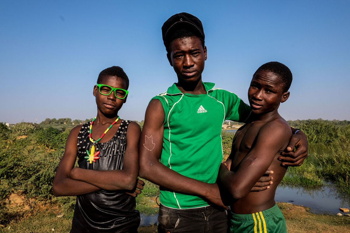 Karim, Moumine and Majid of the 'Jeune Star Boys' group show off their tattoos - letters representing the names of group members. The boys hang out along the banks of the Niger River nearly every day, they say. [Ricci Shryock/Al Jazeera]