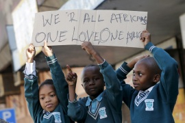 Schoolchildren hold a placard during a march against xenophobia in downtown Johannesburg in April 2015 [Mike Hutchings/Reuters]