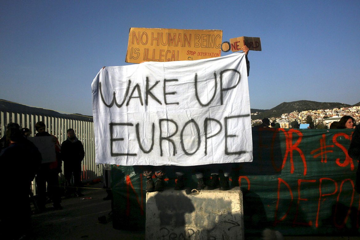 Activists hold banners as they protest the deportations, at the port of Mytilene on the Greek island of Lesbos. [Giorgos Moutafis/Reuters]