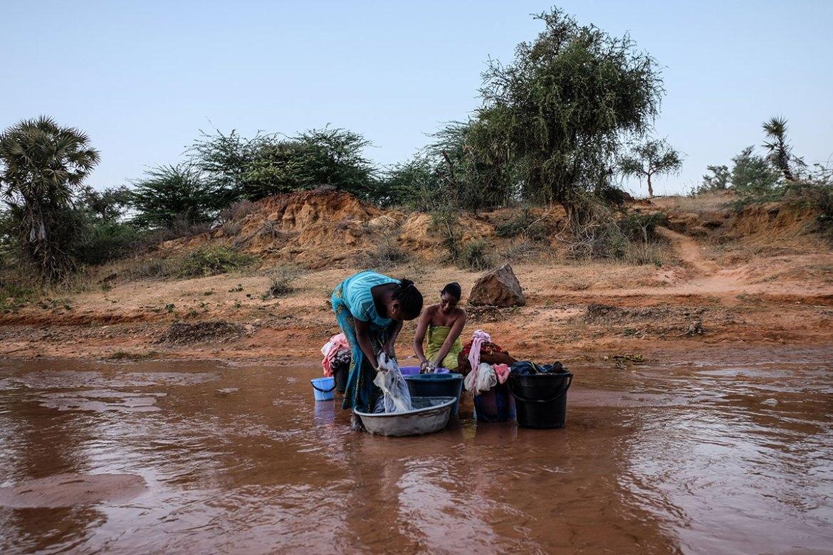 Halima, 19, washes clothes in the Niger River just outside of Niamey. She has two children. [Ricci Shryock/Al Jazeera]