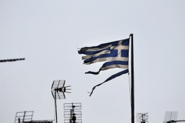 A frayed Greek national flag flutters among antennas atop a building in central Athens, Greece [REUTERS]
