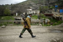 A volunteer walks on a road in the Nagorno-Karabakh's village of Talish. [Reuters]