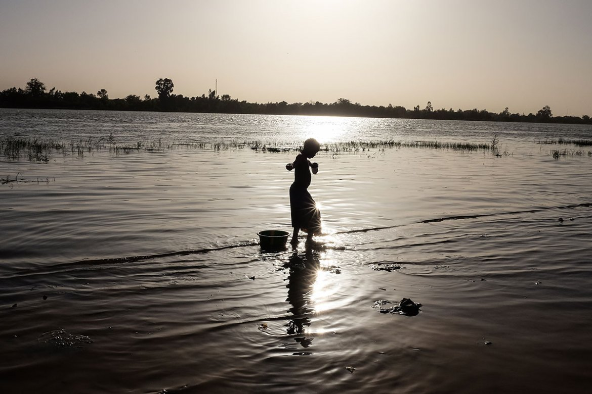 A girl washes clothes at sunset along the Niger River in Niamey. [Ricci Shryock/Al Jazeera]