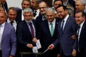 The new leader of the AKP, Binali Yildirim [centre] poses with MPs as he casts his vote during a debate to lift the immunity of Turkish parliamentarians [Reuters]