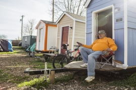 Peter Regan takes a break outside of his tiny home at the Green Street Church in Nashville [Joe Buglewicz/Al Jazeera]