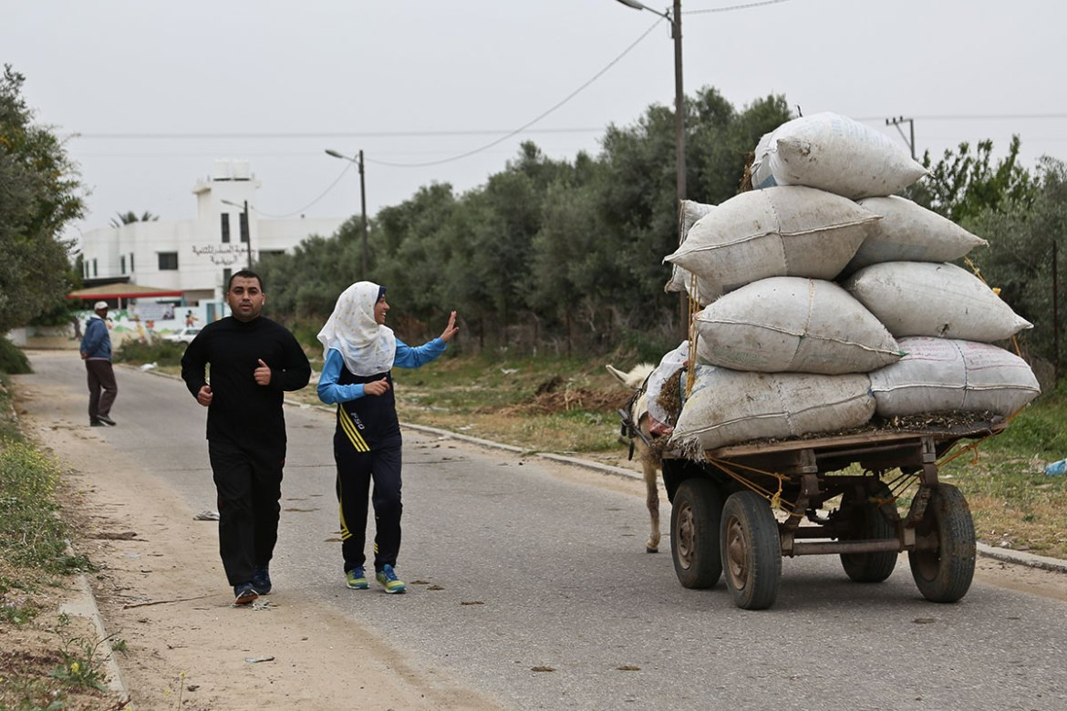 Two Bedouin women call out in encouragement as Nofal passes them. 'At first I was nervous to run in the streets, but most people are supportive,' she said. [Lena Odgaard/Al Jazeera]