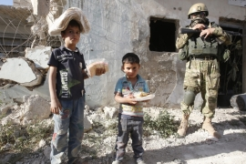 Syrian children holding bread and sweets from an Russian army aid delivery stand next to a soldier in Kaukab, Hama province, Syria [EPA]