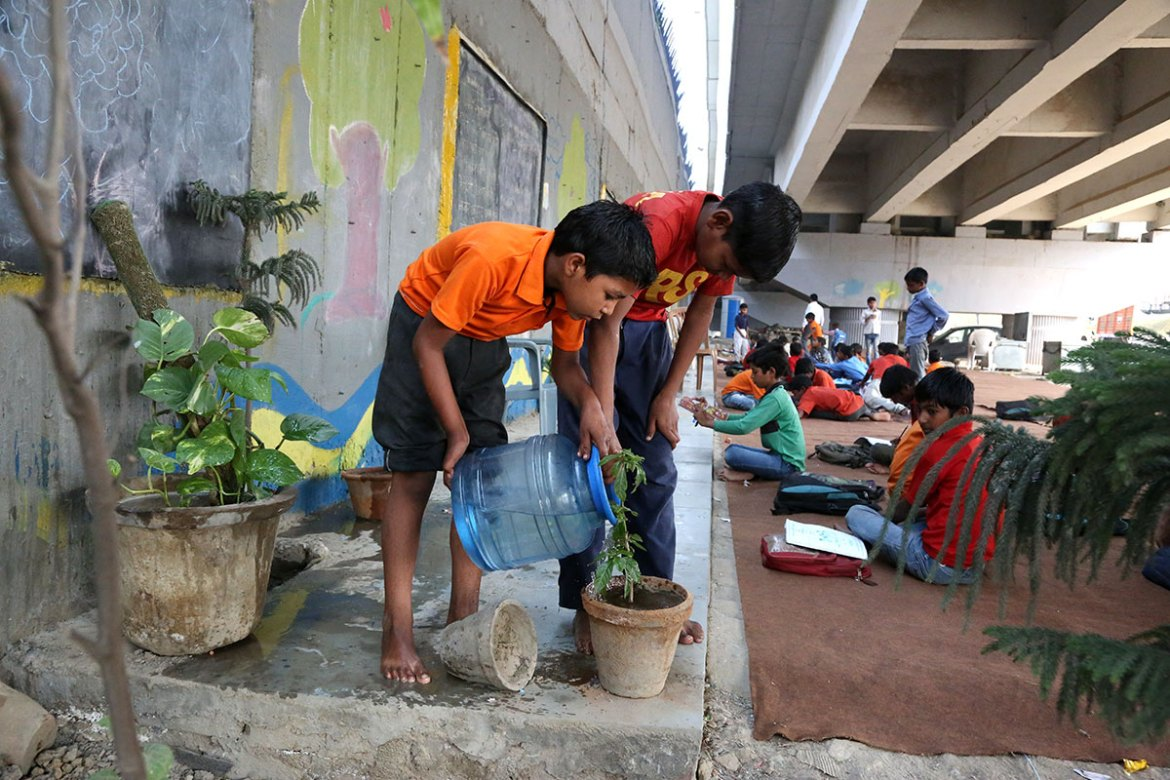 Pupils help to clean up before class begins. [Showkat Shafi/Al Jazeera]