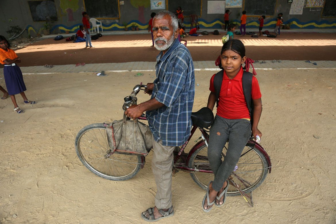 Fifty-five-year-old Ramesh Chander rides three kilometres on his bicycle each day to take his granddaughter, Lalita Kumari, to the school under the bridge. [Showkat Shafi/Al Jazeera]