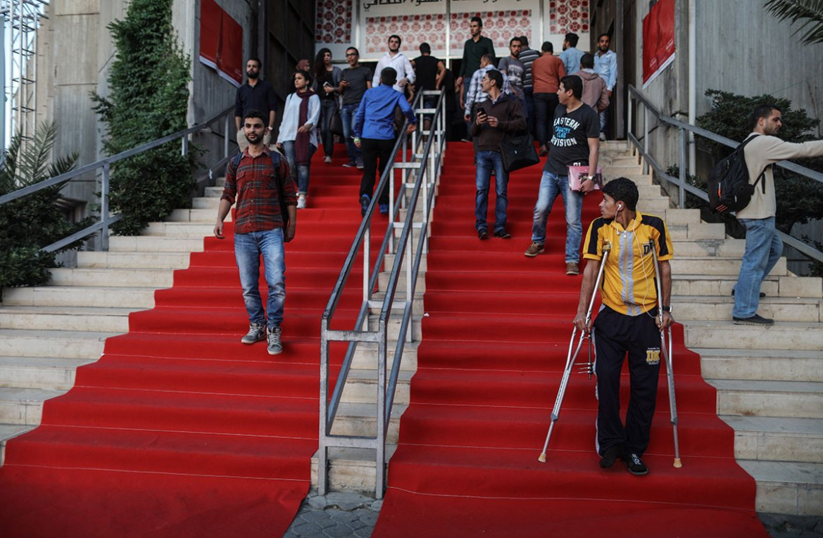 A Palestinian man wounded in the 2014 Israeli war on Gaza walks the red carpet after attending the film festival this weekend. [Wissam Nassar/Al Jazeera]