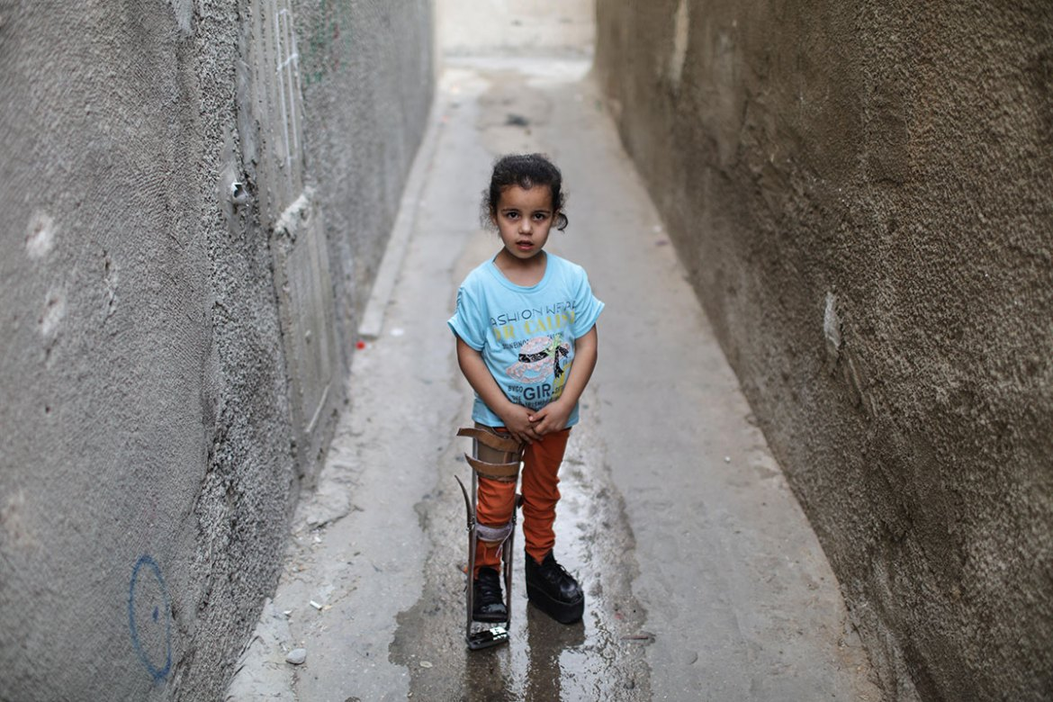 Rama, a young Palestinian refugee, stands in an alley near her family's home. [Wissam Nassar/Al Jazeera]