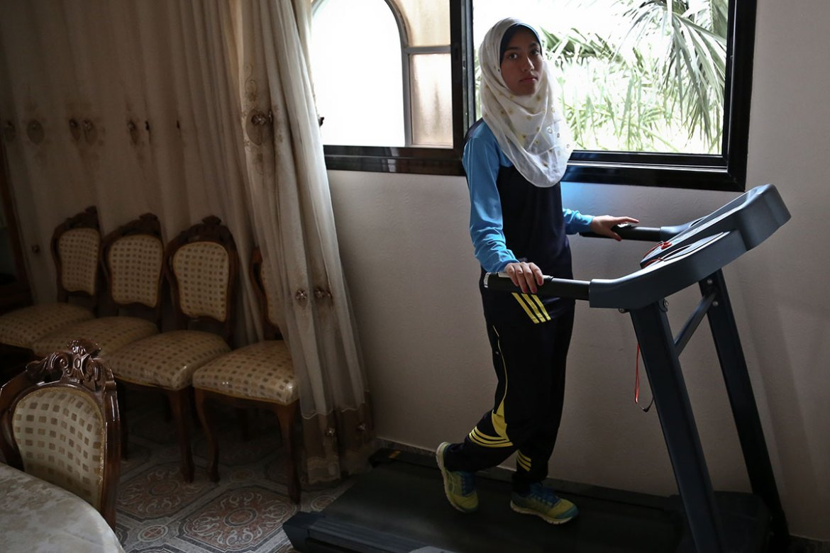 Nofal has a treadmill in her living room, which she uses twice a week. Owing to daily power cuts of 12 hours or more, she has to adapt her training to when electricity is on. 'Sometimes I wait until 10pm, and sometimes the power cuts while I'm running - it can be a nice break, though,' she says, laughing. [Lena Odgaard/Al Jazeera]
