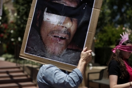A protester holds a photo from Abu Ghraib prison while demonstrating against a lack of justice [Jae C Hong/AP]