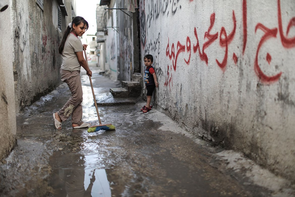 Palestinian refugees clean the streets of the Jabalia camp. [Wissam Nassar/Al Jazeera]