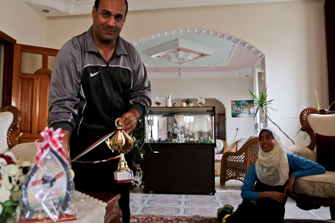 Nofal's father, Mahmoud, is her greatest supporter. He proudly shows off medals she has won in local competitions. [Lena Odgaard/Al Jazeera]