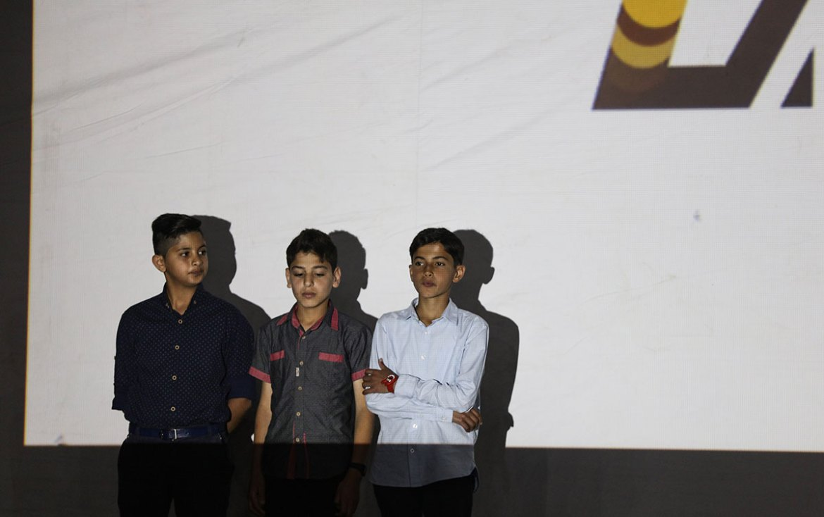 Three Palestinian child actors stand on stage during the festival. [Wissam Nassar/Al Jazeera]