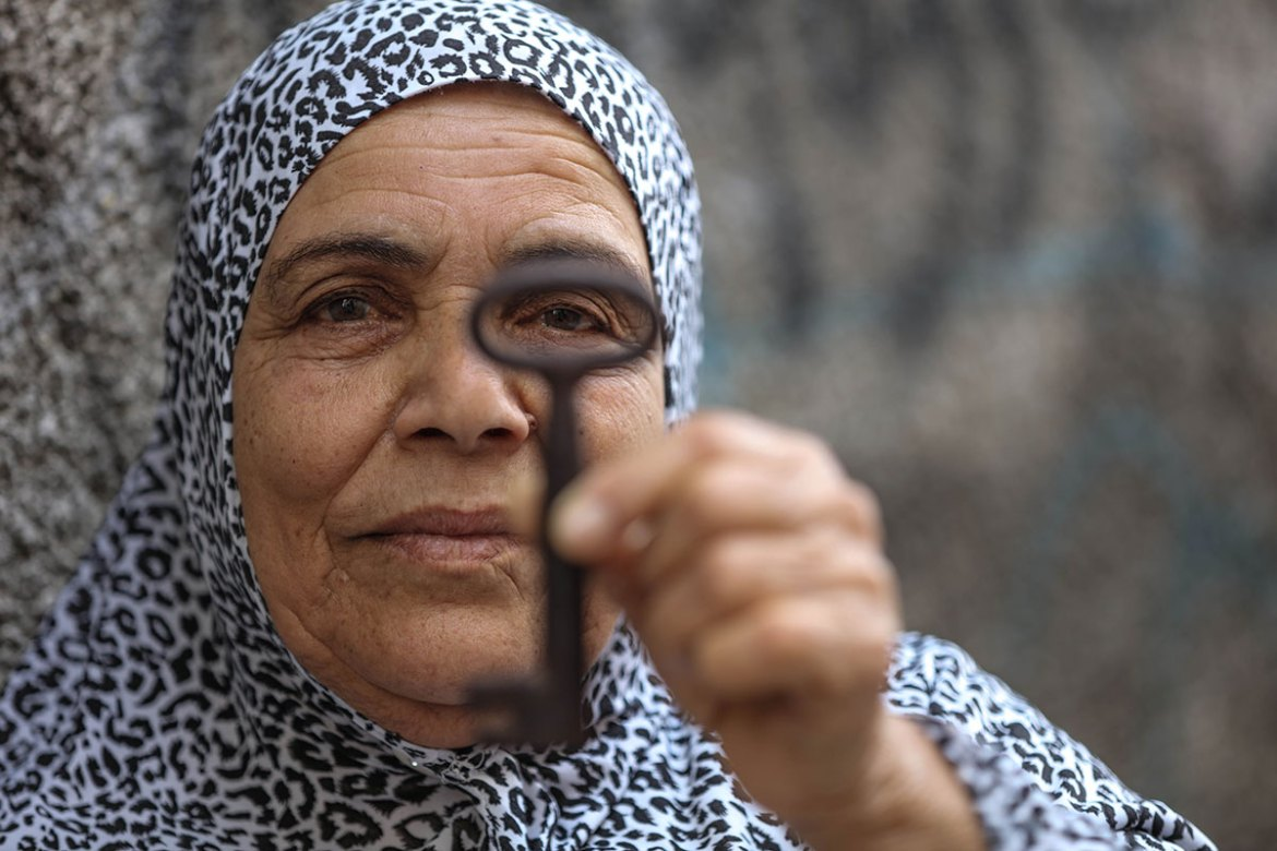 Fatma Abuqamar, 70,  holds up her old house key, a reminder of her  village, Hamama. [Wissam Nassar/Al Jazeera]